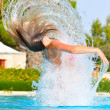 slim woman is jumping and throwing wet hair back in swimming poo — Stock Photo