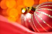 Bolas decorativas de natal na seda vermelha contra luzes desfocadas — Fotografia Stock