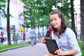 Bella donna è seduta in città con laptop e guardando ca — Foto Stock