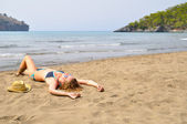 Sexy woman is lying on the wild beach — Stock Photo
