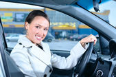 Happy business woman in a car is looking at camera — Stock Photo