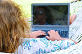 Woman is lying in hammock and working on laptop — Zdjęcie stockowe