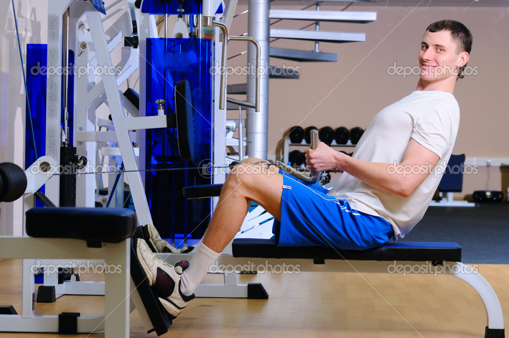 Young handsome man is training in gym using a rower  Stock Photo #4350694