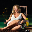 Sensual woman is sitting on chair at poolside at night and looki — Stock Photo #4481918