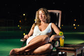 Sensual woman is sitting on chair at poolside at night and looki — Stock Photo