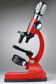 Red microscope on gray background — Stock Photo