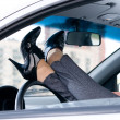 Slim female legs are lying on steering wheel - Stock Photo