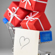 Closeup of a shopping cart with gifts and heart — Stock Photo #4748945