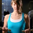 Stock Photo: Beautiful woman is exersising in gym at evening
