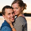 Stock Photo: Young attractive couple near lake at sunset