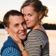 Young attractive couple near lake at sunset — Stock Photo