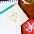Top view of a office workplace with gift, champagne and heart — Stock Photo