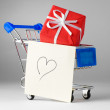 Closeup of a shopping cart with gifts and heart — Stock Photo
