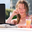 Sensual young woman with laptop in swimming pool with cocktail — Stock Photo