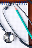 Stethoscope with pen on a notepad — Stock Photo
