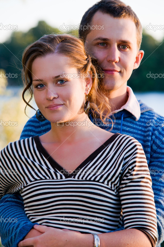 Young attractive couple near lake at sunset  Stock Photo #4892077
