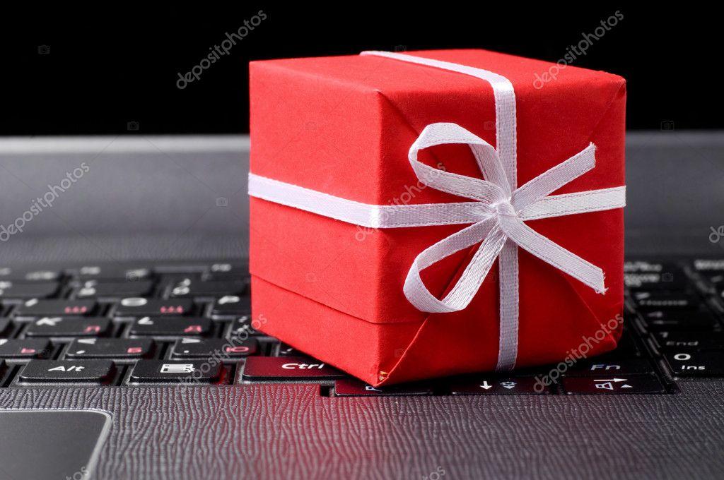 笔记本电脑键盘上的红色礼品盒– 图库图片