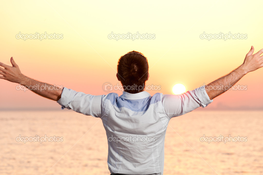 Businessman is standing near the sea at sunrise — Stock Photo #5267405