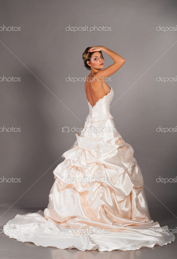 Beautiful bride is standing in wedding dress on grey background, side view  Stock Photo #5339615