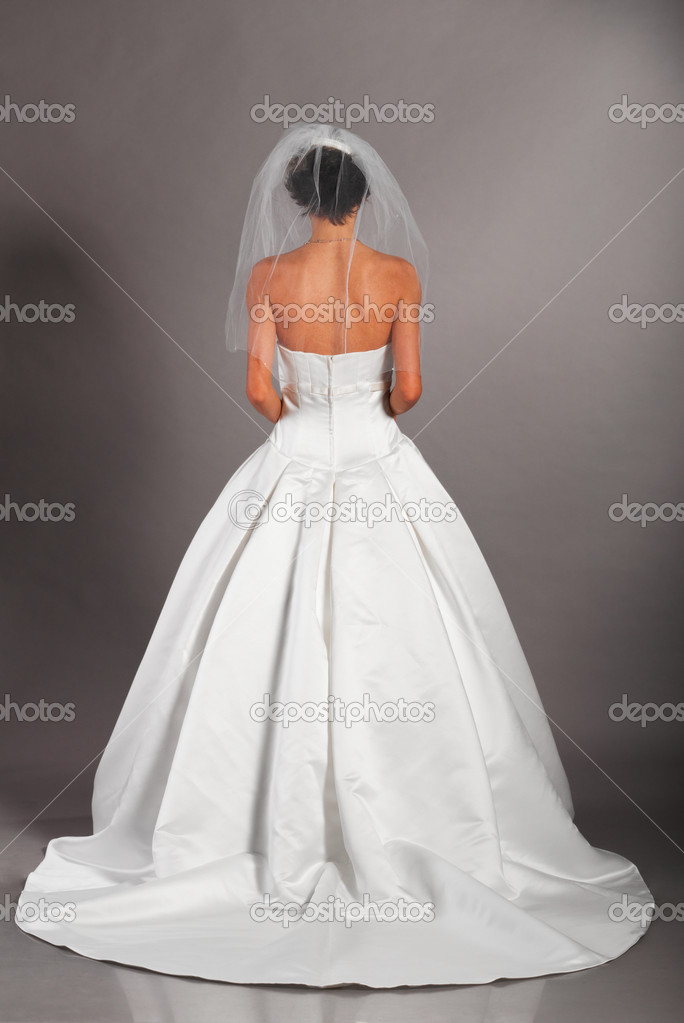 Beautiful bride is standing in wedding dress on grey background, view from behind  Stock Photo #5349721