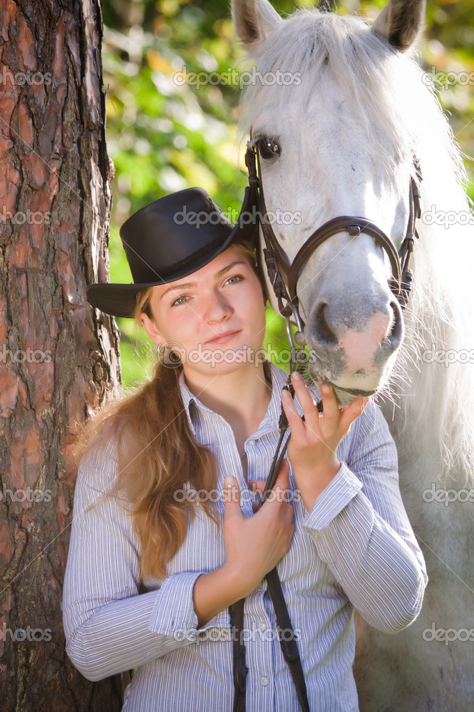 Young Lady in hat hugging her horse  Stock Photo #4090726