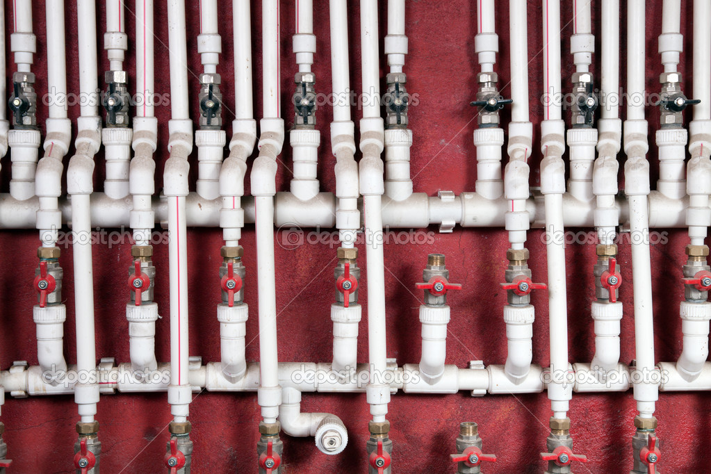 White water pipes against a red wall — Zdjęcie stockowe #4747749