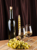 Bottle, glass with wine and candle — Stock Photo
