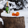 Bottle of champagne, glasses, oranges on to snow — Stock Photo