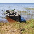 Old wooden boat on lake bank, north Russia - Stock Photo