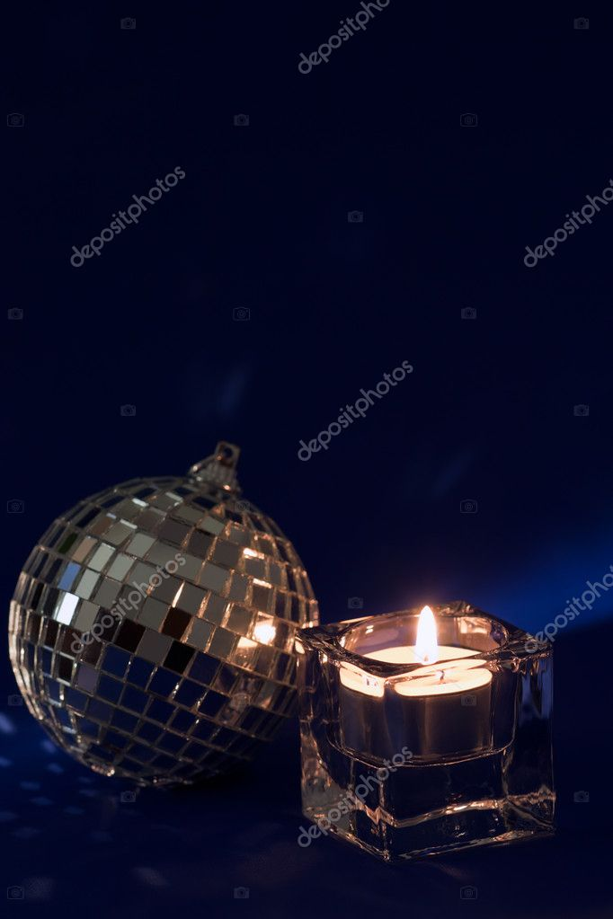 Shiny silver bauble and Christmas candle on a dark blue background — Stock Photo #4222963