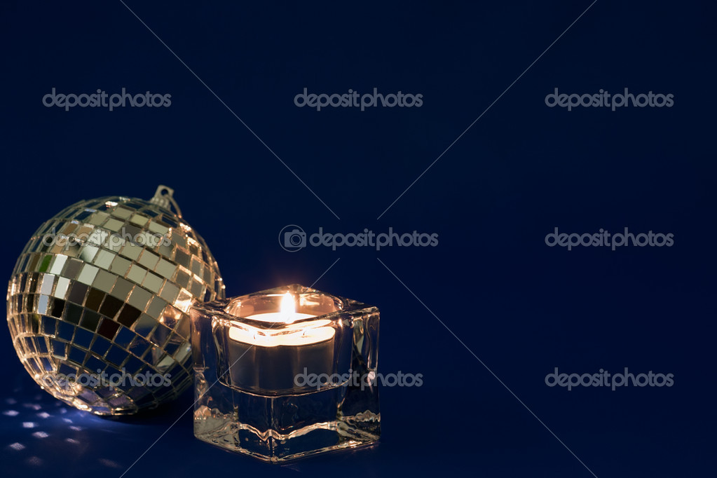 Shiny silver bauble and Christmas candle on a dark blue background — Stock Photo #4222973