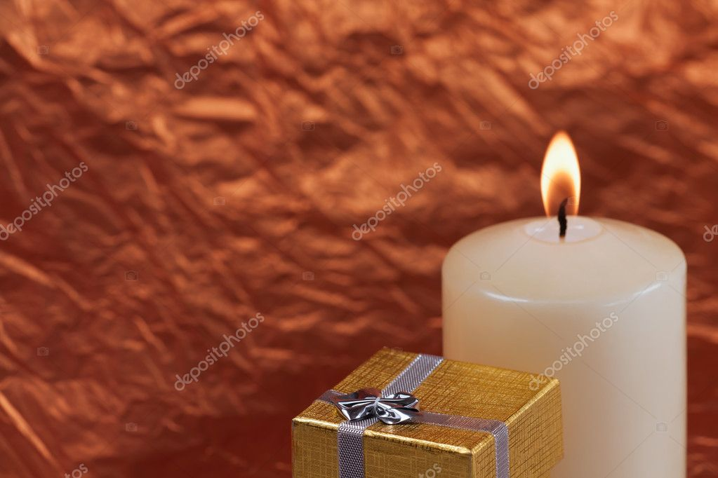 Christmas gift and white candle on a red background — Stock Photo #4266971