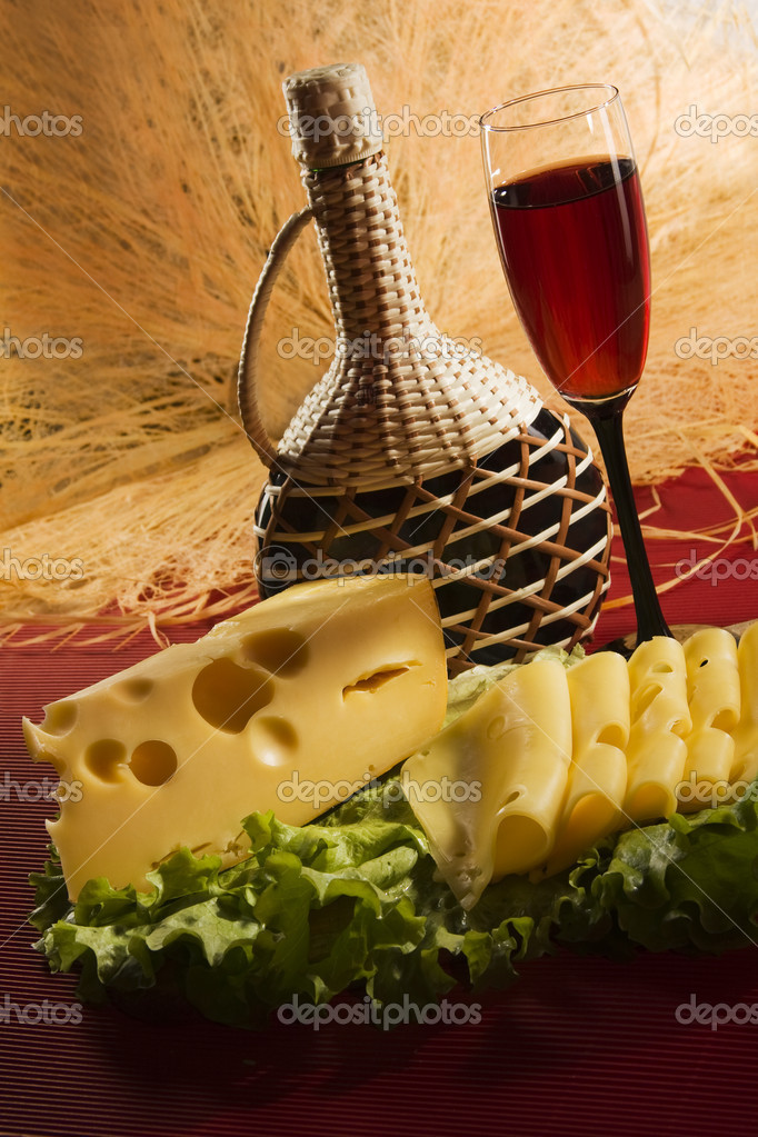 Red wine glass, bottle and slices of cheese — Stock Photo #5137499