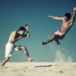 Two young men sport fighting on beach — Stock Photo