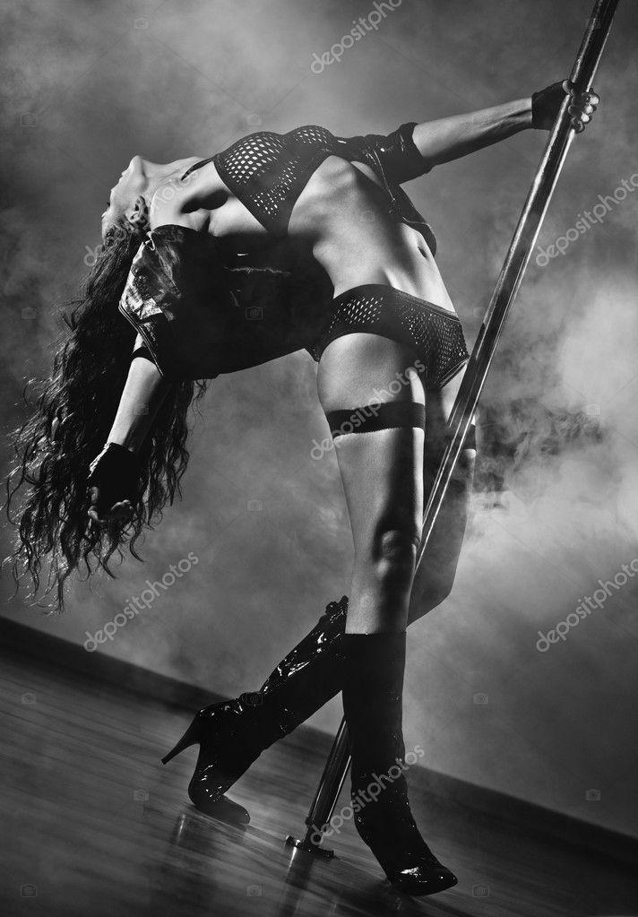 Сексуальная девушка танцует с шестом в дыму, тонировано.
