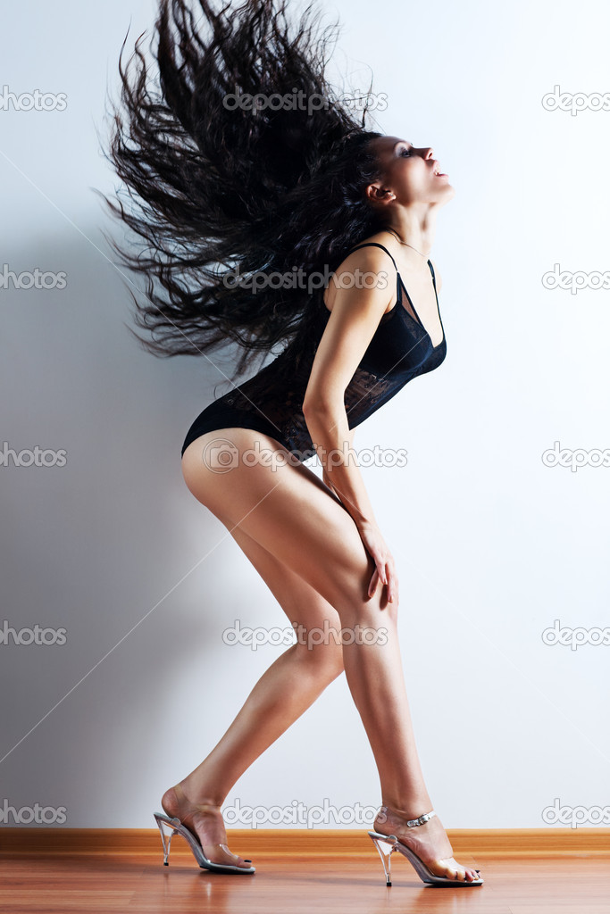 Young woman shaking hair. On wall background.  Stock Photo #4698400