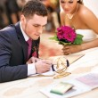 Young couple signing wedding documents - Stockfoto