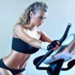 Young woman on exercise bicycle — Stock Photo #5040381