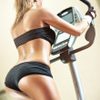 Young woman on exercise bicycle — Stock Photo