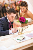 Young couple signing wedding documents — 图库照片