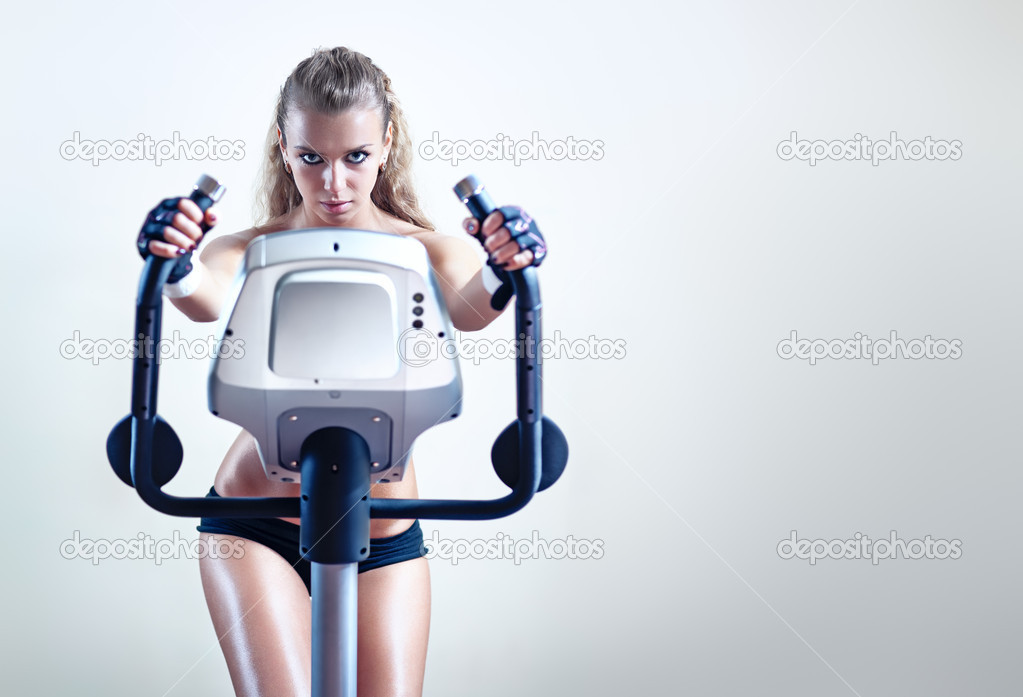 Young woman on exercise bicycle on wall background. — Stock Photo #5040390