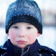 The sad crying boy with blue eyes in winter clothes — Stock Photo