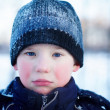 Royalty-Free Stock Photo: The sad crying boy with blue eyes in winter clothes