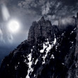 Photo: Moonlit night and clouds on night sky in the mountains