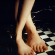 Feet of a woman on chess board with black background — Stock Photo