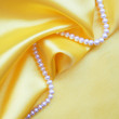 Smooth elegant golden silk with pearls — Stock Photo