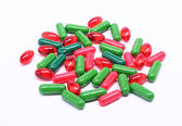 Red and green pills on white background — Stock Photo