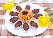 Ciasto i czekoladki na białe płytki z dwoma żonkile — Zdjęcie stockowe