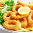Deep batter fried squid rings calamari with green salad - Stock Photo