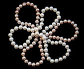 Flower of white and pink pearls on a black silk — Stock Photo